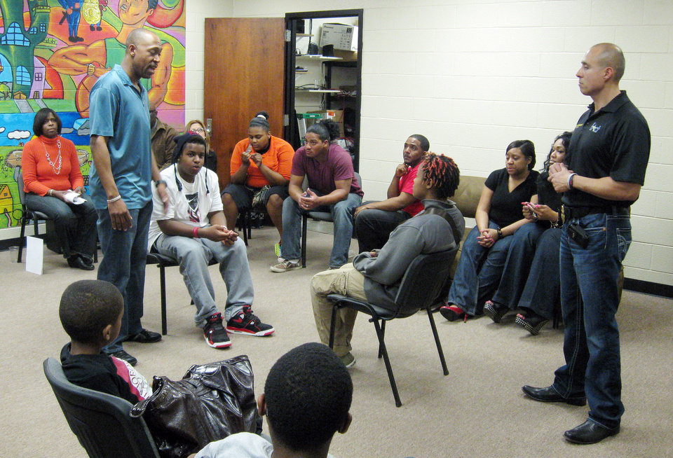 Photo - Oklahoma City police Sgt. Wayland Cubit and Sgt. Fernando Hernandez discuss conflict resolution with youth during the weekly FACT meeting at the Hathaway Center.  Photos by MATT DINGER, The Oklahoman