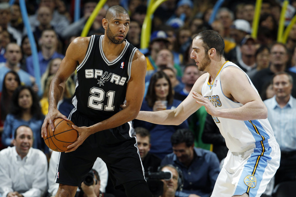 San Antonio Spurs center Tim Duncan (21) looks to pass the ball as Denver Nuggets forward Kosta Koufos defends in the first quarter of an NBA basketball game in Denver, Wednesday, April 10, 2013. (AP Photo/David Zalubowski)