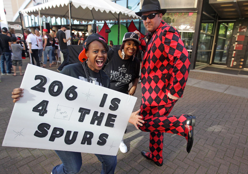 Photo - San Antonio Spurs fans Nicol Mack, left, Shantae Duckworth, center, pose for a photo with Portland Trail Blazers fan Scott Cummins before Game 4 of a Western Conference semifinal NBA basketball playoff series Monday, May 12, 2014, in Portland, Ore. (AP Photo/Rick Bowmer)