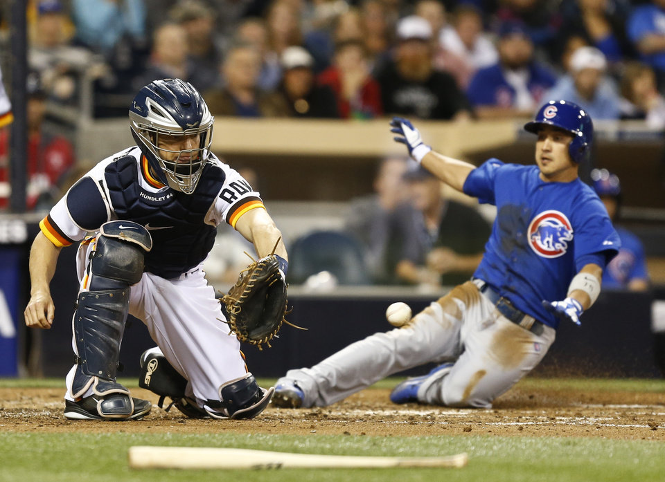 Photo - San Diego Padres catcher Nick Hundley waits on the late throw as Chicago Cubs' Darwin Barney slides in safely in the fifth inning of a baseball game Thursday, May 22, 2014, in San Diego.  (AP Photo/Lenny Ignelzi)