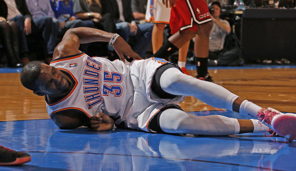 Photo - Oklahoma City's Kevin Durant (35) grabs his side after falling to the ground during an NBA basketball game between the Oklahoma City Thunder and the Miami Heat at Chesapeake Energy Arena in Oklahoma City, Thursday, Feb. 15, 2013. Miami won 110-100. Photo by Bryan Terry, The Oklahoman