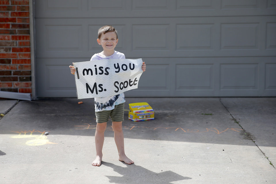 Photo - Noah Garvie, 6, an Oakridge Elementary kindergarten student, holds a sign as he waits for an Oakridge Elementary faculty caravan through neighborhoods around the Moore school, Tuesday, March 24, 2020. [Bryan Terry/The Oklahoman]