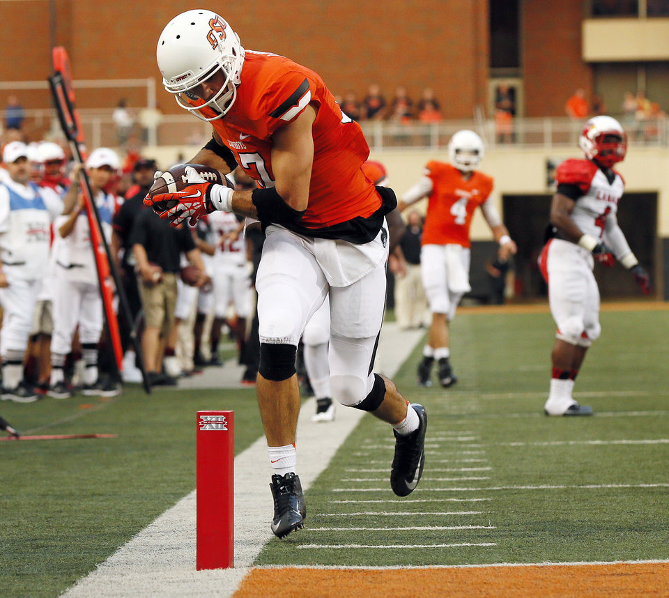 Photo - Oklahoma State's Charlie Moore (17) takes the ball to the 1-yard line in the first quarter during a college football game between the Oklahoma State University Cowboys (OSU) and the Lamar University Cardinals at Boone Pickens Stadium in Stillwater, Okla., Saturday, Sept. 14, 2013. Photo by Nate Billings, The Oklahoman