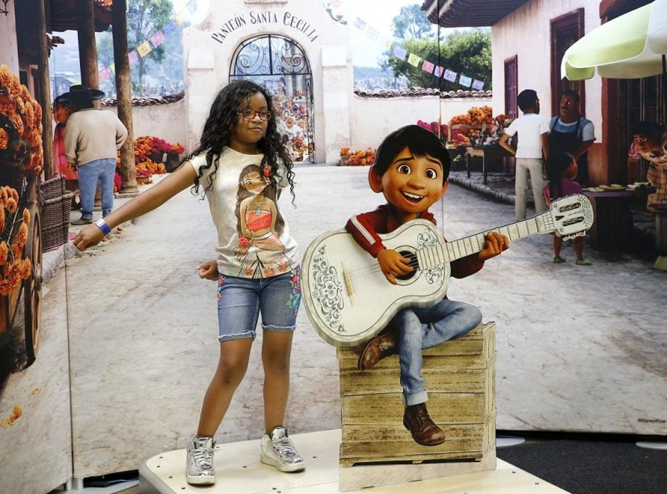 "Photo - Jennavecia Alfaro, 8, of Lawton, Okla., dances next to Miguel from Coco before the opening performance of ""Disney on Ice presents Dare to Dream"" at the Jim Norick Arena during the  Oklahoma State Fair in Oklahoma City, Thursday, Sept. 13, 2018. Photo by Sarah Phipps, The Oklahoman"
