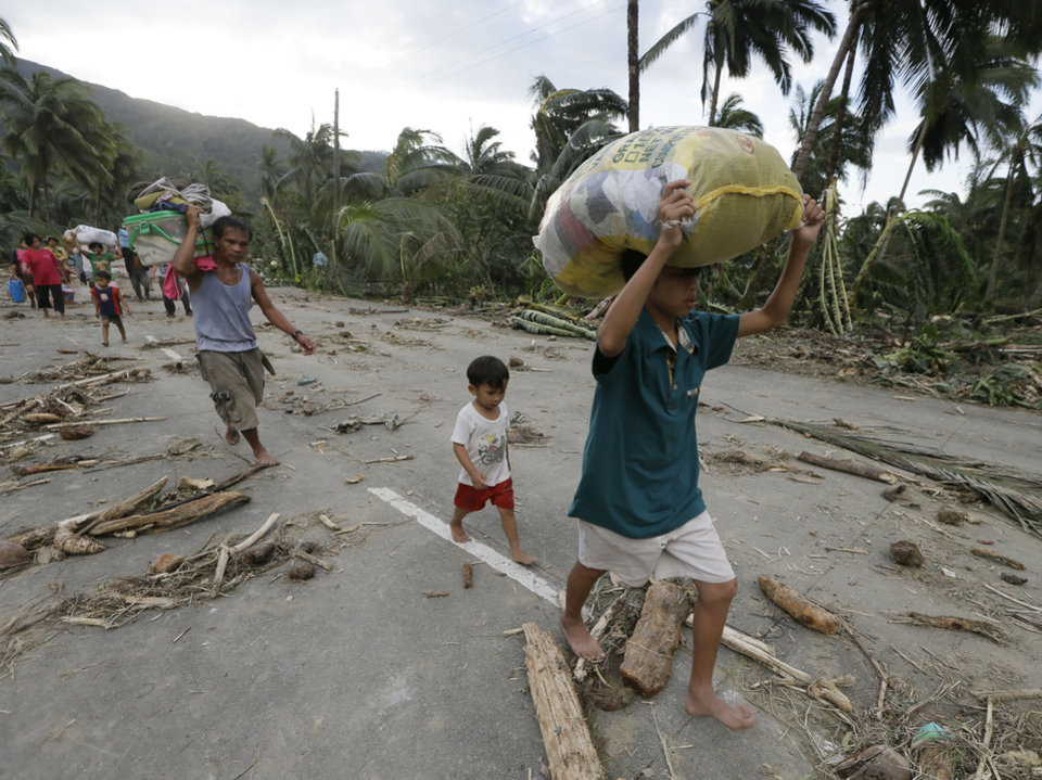 Residents walk to an evacuation center after retrieving their belongings at the flash flood-hit village of Andap, New Bataan township, Compostela Valley in southern Philippines, Wednesday Dec. 5, 2012.  Typhoon Bopha, one of the strongest typhoons to hit the Philippines this year, barreled across the country's south on Tuesday, killing scores of people while triggering landslides, flooding and cutting off power in two entire provinces. (AP Photo/Bullit Marquez)