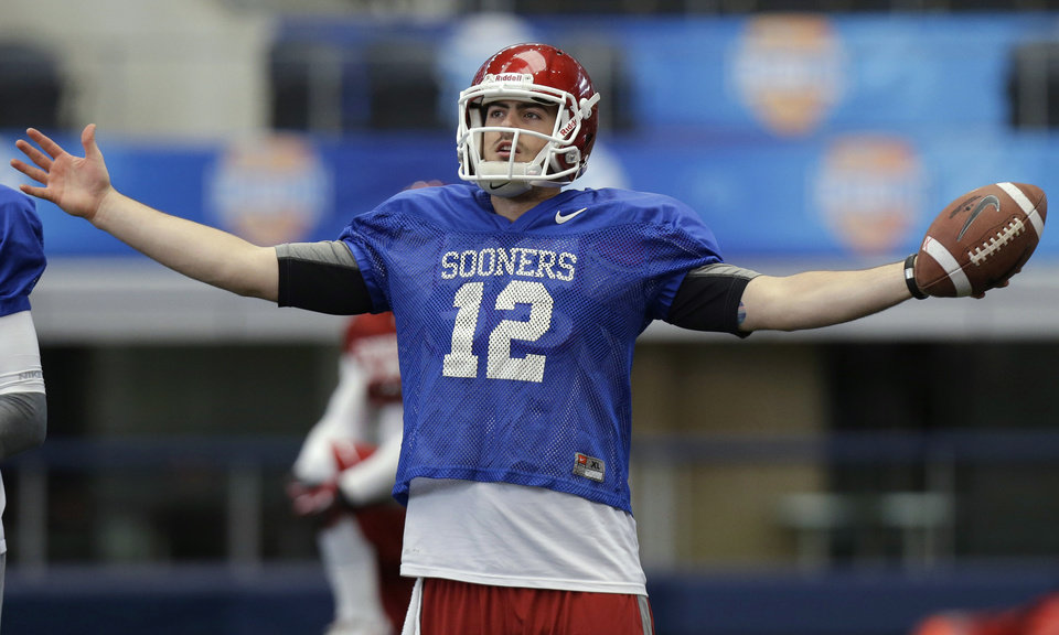 Photo - Oklahoma quarterback Landry Jones holds a football during practice after media day for Friday's Cotton Bowl NCAA college football game against Texas A&M, at Cowboys Stadium, Sunday, Dec. 30, 2012, in Arlington, Texas. (AP Photo/LM Otero)