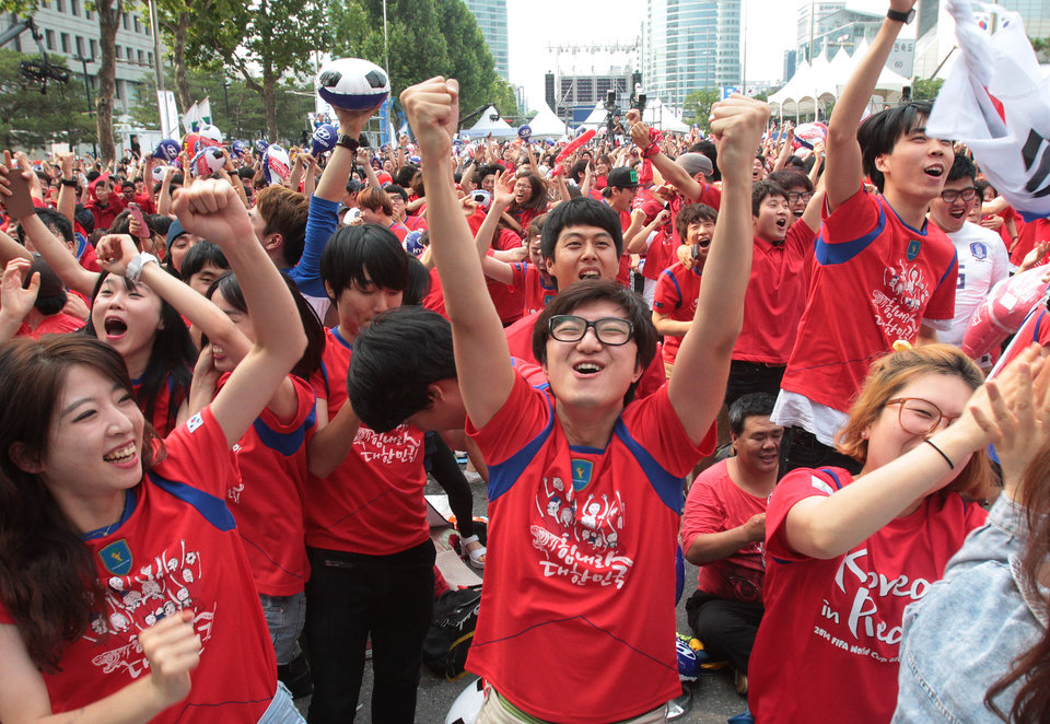 Photo - South Korean soccer fans celebrate after their soccer team scored the first goal against  Russia during the group H World Cup soccer match between Russia and South Korea, at a public viewing venue in Seoul, South Korea, Wednesday, June 18, 2014.(AP Photo/Ahn Young-joon)