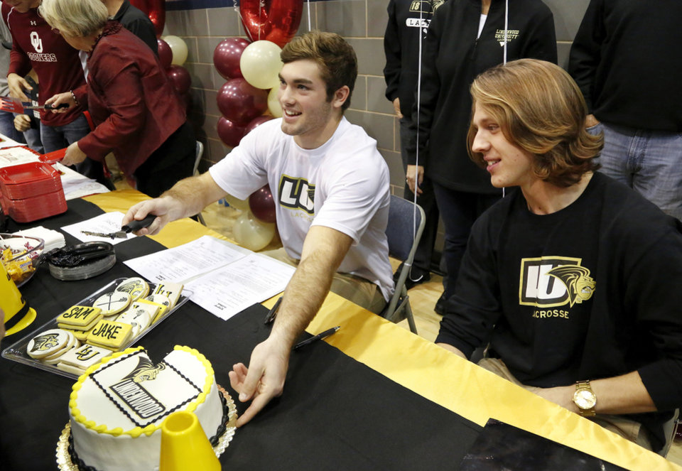 Jake Hobbs, left, and Sam Heaton share cake with students after signing  letters to play lacrosse at Lindenwood. Athletes from Edmond North High School signed national letters of intent with colleges and universities during a ceremony in the school's gymnasium Wednesday morning, Nov. 13, 2013. Various sports include golf, softball, wrestling,  lacrosse and others. Photo by Jim Beckel, The Oklahoman