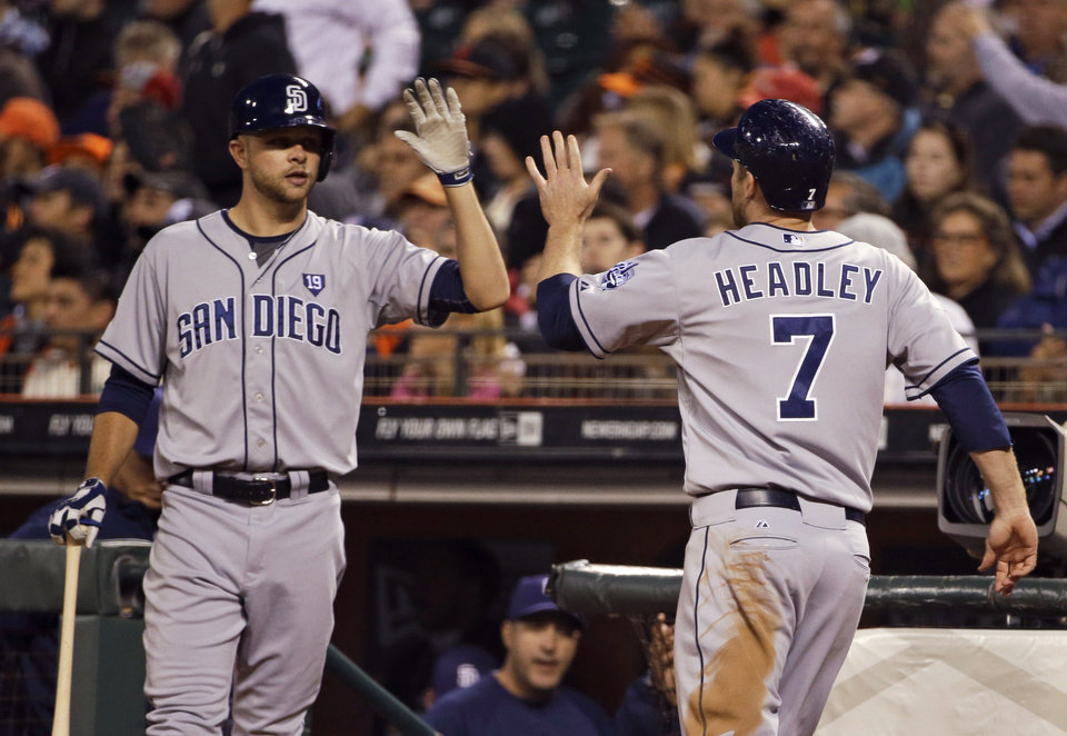 Photo - San Diego Padres' Chase Headley, right, is greeted by Jesse Hahn, left, after scoring in the sixth inning of a baseball game against the San Francisco Giants on Tuesday, June 24, 2014, in San Francisco. (AP Photo/Eric Risberg)