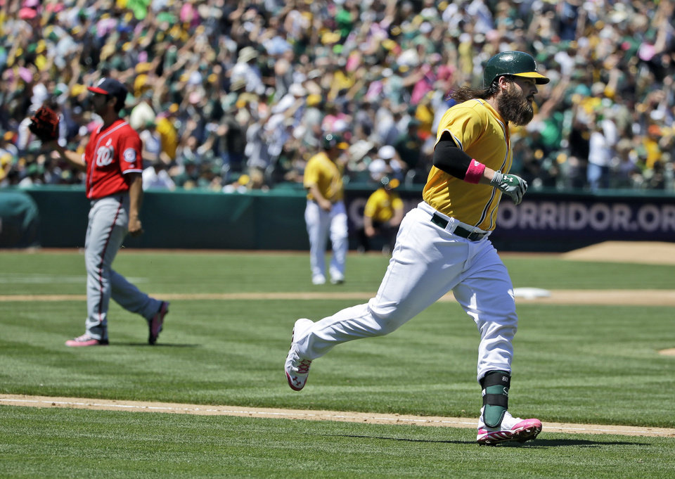 Photo - Oakland Athletics' Derek Norris, right, runs down the first base line after his second three-run home run of a baseball game against Washington Nationals pitcher Gio Gonzalez, left, during the second inning on Sunday, May 11, 2014, in Oakland, Calif. (AP Photo/Marcio Jose Sanchez)