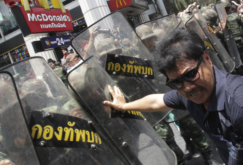 Photo - An anti-coup protester clashes with Thai soldiers during a demonstration in Bangkok, Thailand, Sunday, May 25, 2014. The top general in Thailand's ruling junta warned people Sunday not to join anti-coup street protests, saying normal democratic principles cannot be applied at the time, as troops fanned out in central Bangkok to prevent rallies.(AP Photo/Sakchai Lalit)