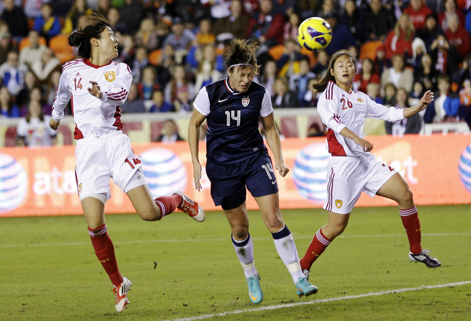 United States' Abby Wambach heads a ball past China's Wang Dongni and Wu Haiyan (26) for a goal during the first half of an exhibition soccer match, Wednesday, Dec. 12, 2012, in Houston. (AP Photo/David J. Phillip)
