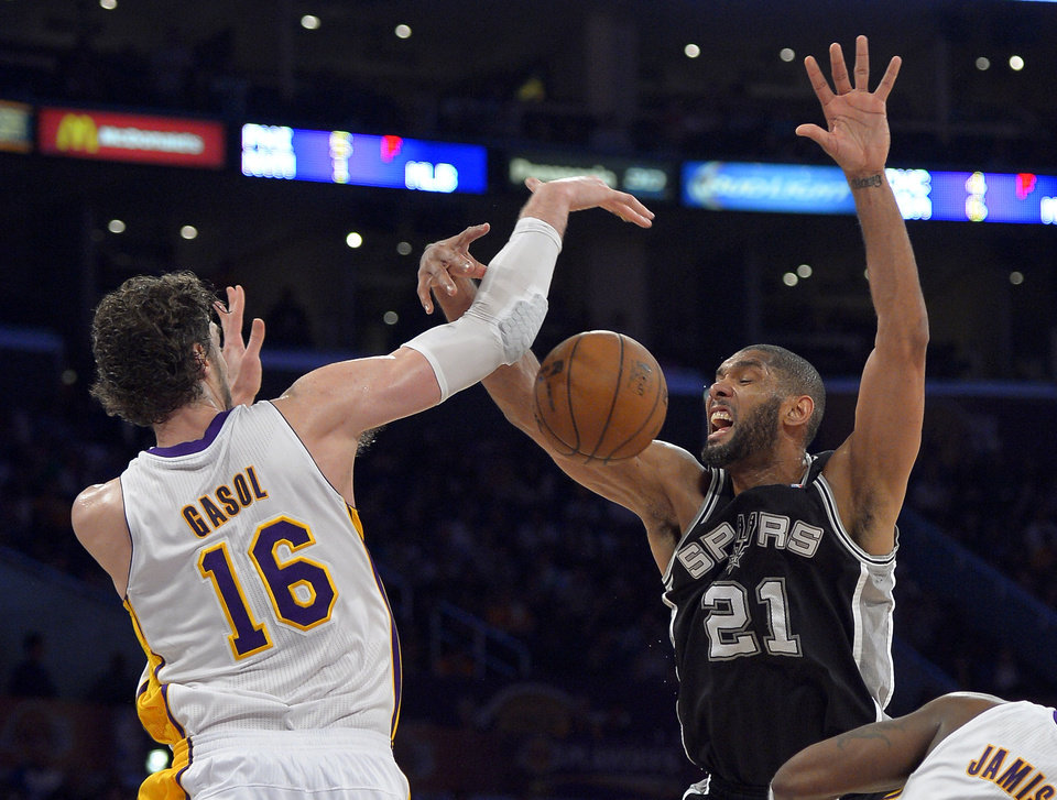 Photo - Los Angeles Lakers forward Pau Gasol (16), of Spain, knocks the ball out of the hands of San Antonio Spurs forward Tim Duncan during the second half in Game 4 of a first-round NBA basketball playoff series, Sunday, April 28, 2013, in Los Angeles. The Spurs won 103-82. (AP Photo/Mark J. Terrill)
