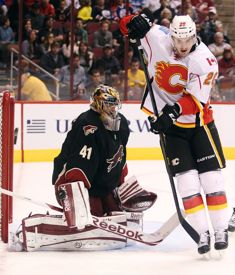 Photo - Phoenix Coyotes goalie Mike Smith (41) makes a blocker save as Calgary Flames left winger Curtis Glencross, right, sets a screen in the first period of an NHL hockey game, Monday, Feb. 18, 2013, in Glendale, Ariz. (AP Photo/Paul Connors)