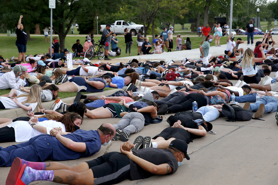 Photo - Protesters lie face down outside the Norman Police Department in Norman, Okla., Tuesday, June 2, 2020, in response to the death of George Floyd. [Sarah Phipps/The Oklahoman]