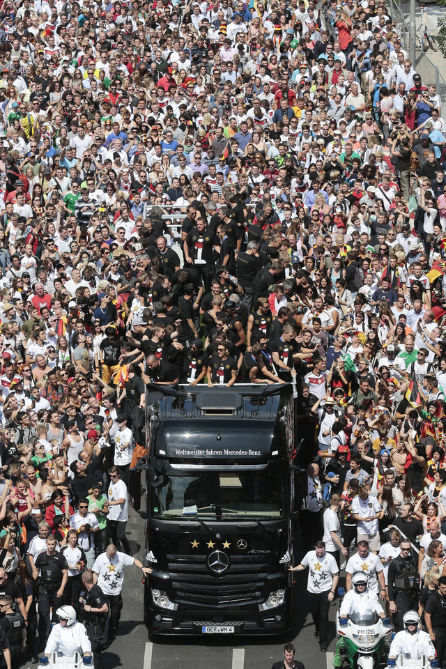 """Photo - The German soccer squad  arrives in central Berlin Tuesday, July 15, 2014. Germany's World Cup-winning team has returned home  from Brazil to celebrate the country's fourth title with huge crowds of fans. The team's Boeing 747 touched down at Berlin's Tegel airport midmorning Tuesday after flying a lap of honor over the """"fan mile"""" in front of the landmark Brandenburg Gate.  (AP Photo/Markus Schreiber)"""