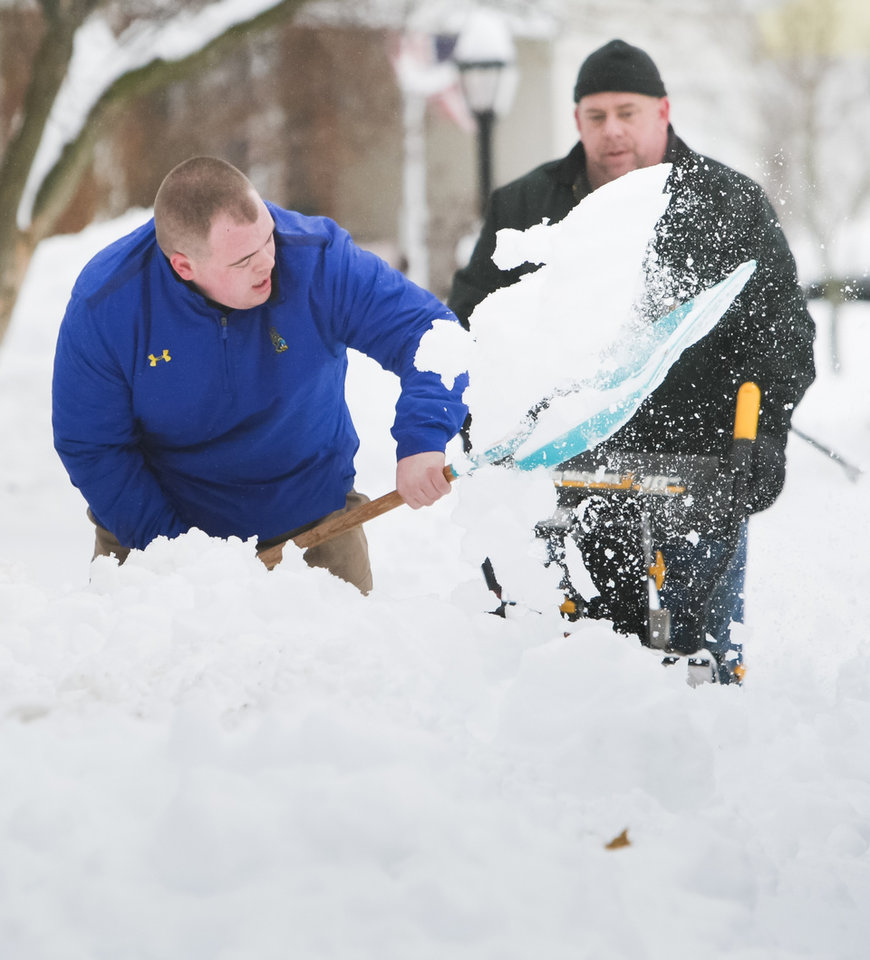 Photo - James Farley of Hockessin digs over a foot of snow from his sidewalk and driveway with the help from his dad, Brandt as snow will continue to fall in New Castle County, Thursday, Feb, 13, 2014, in Hockessin, Del. (AP Photo/The News Journal, Suchat Pederson)