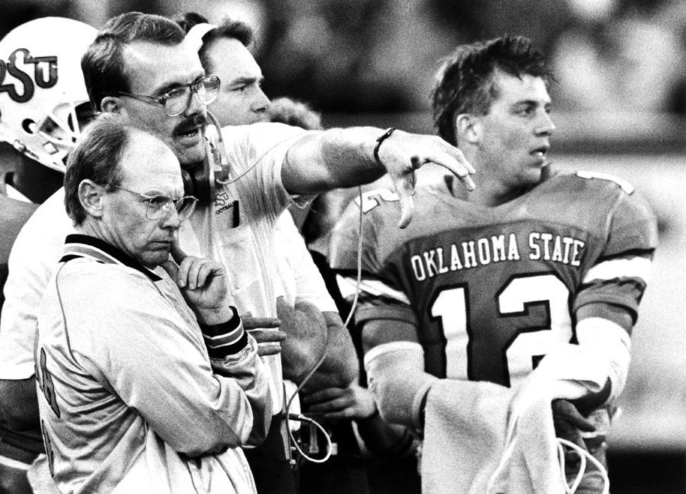 "Photo -  COLLEGE FOOTBALL: ""OSU head coach Pat Jones, left, talks with an assistant coach as quarterback Mike Gundy looks on Saturday"" during the Oklahoma State University-Texas A&M game in Stillwater.  The Cowboys won handily, 52-15. Staff photo by Doug Hoke taken 9/24/88; photo ran in the 9/25/88 Daily Oklahoman."