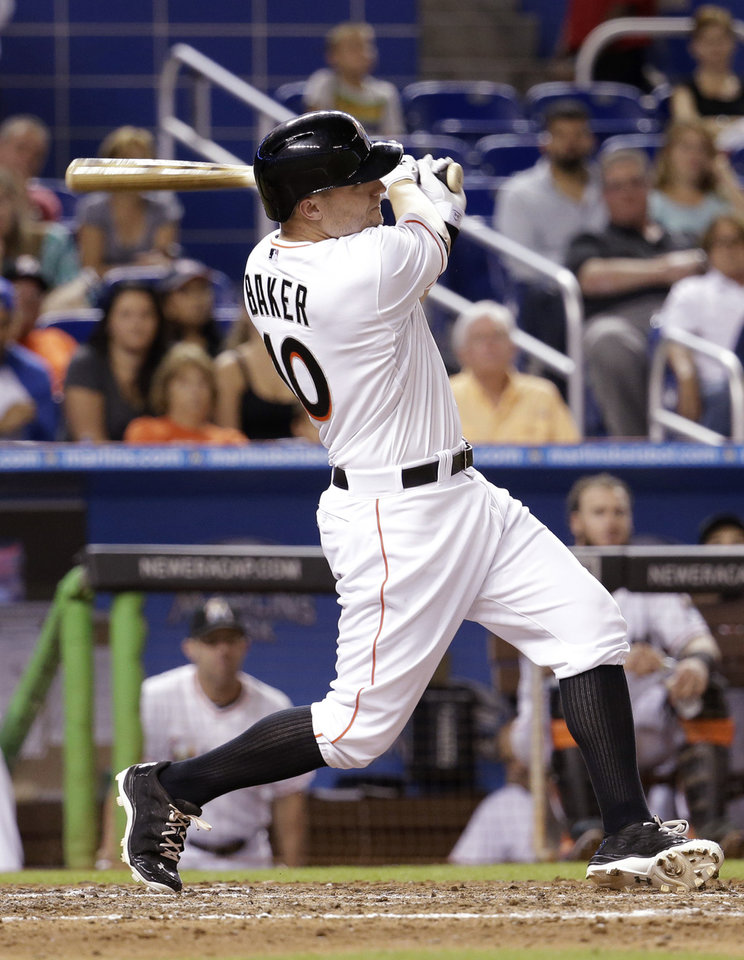 Photo - Miami Marlins' Jeff Baker (10) follows through on a two-run home run in the ninth inning during a baseball game against the St. Louis Cardinals, Wednesday, Aug.13, 2014, in Miami. The Cardinals defeated the Marlins 5-2. (AP Photo/Lynne Sladky)