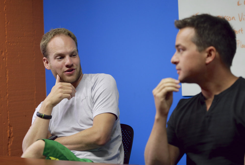 Photo - In this photo from Aug. 14, 2014, David Graff, CEO of Hudl, left, speaks to John Wirtz, Chief Product Officer, in Lincoln, Neb. Hudl is a software company that has developed a way to immediately get game film to coaches after games and break down and separate different plays by type. (AP Photo/Nati Harnik)