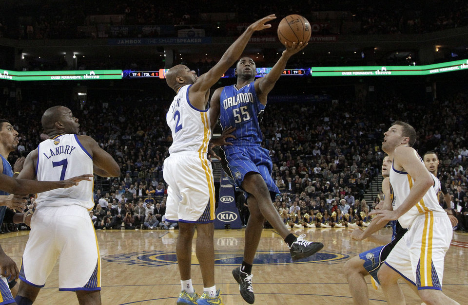 Orlando Magic shooting guard E'Twaun Moore (55) shoots next to Golden State Warriors guard Jarrett Jack (2) during the second quarter of an NBA basketball game in Oakland, Calif., Monday, Dec. 3, 2012. (AP Photo/Jeff Chiu)