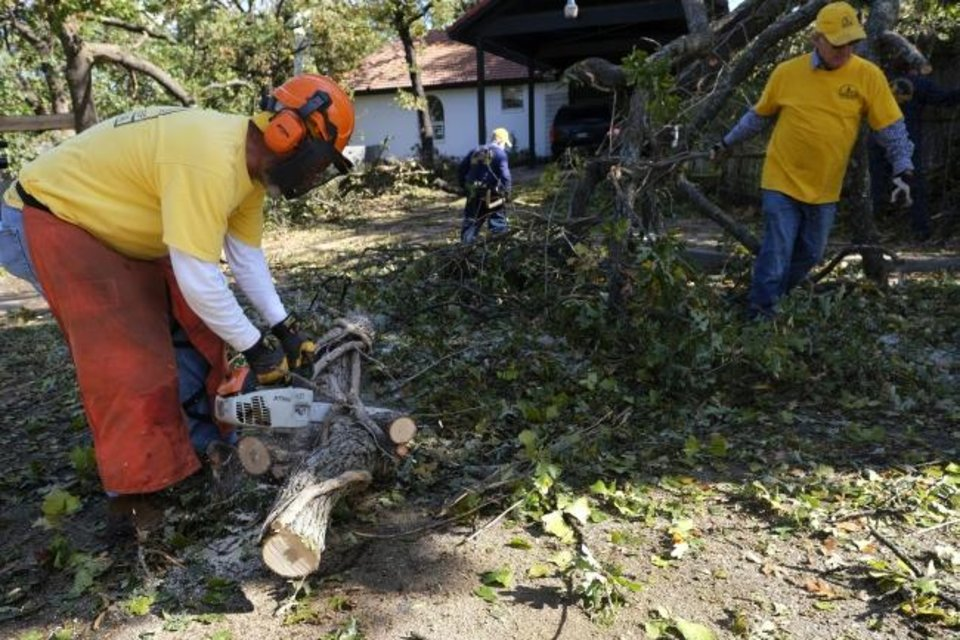 Photo -  An Oklahoma Baptists Disaster Relief team works on tree limb removal at a house in Bethany on Friday. [Doug Hoke/The Oklahoman]