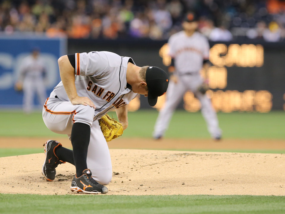 Photo - San Francisco Giants starting pitcher Matt Cain takes a moment to get up after slipping on the mound after delivering a pitch in the first inning of a  baseball game against the San Diego Padres, Friday, April 18, 2014, in San Diego. (AP Photo/Don Boomer)
