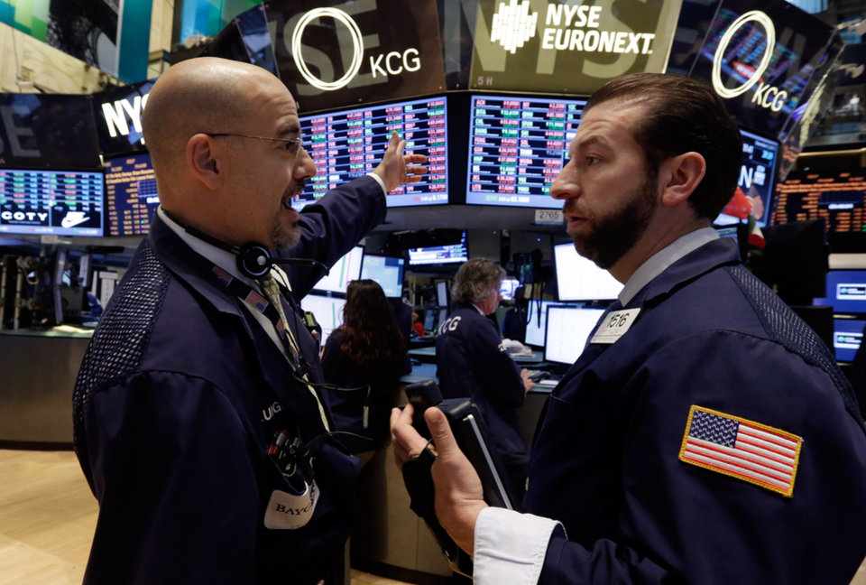 Traders Luigi Muccitelli, left, and Greg Mulligan work on the floor of the New York Stock Exchange Tuesday, Dec. 3, 2013. Stocks are opening lower on Wall Street as investors hold back ahead of economic reports that could influence when the Federal Reserve will start reducing its stimulus. (AP Photo/Richard Drew)