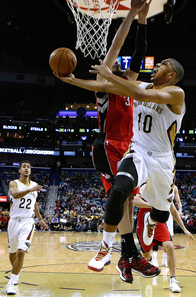 Photo - New Orleans Pelicans guard Eric Gordon (10) drives to the basket against Toronto Raptors guard Nando de Colo (3) during the first half of an NBA basketball game in New Orleans, Wednesday, March 19, 2014. (AP Photo/Jonathan Bachman)