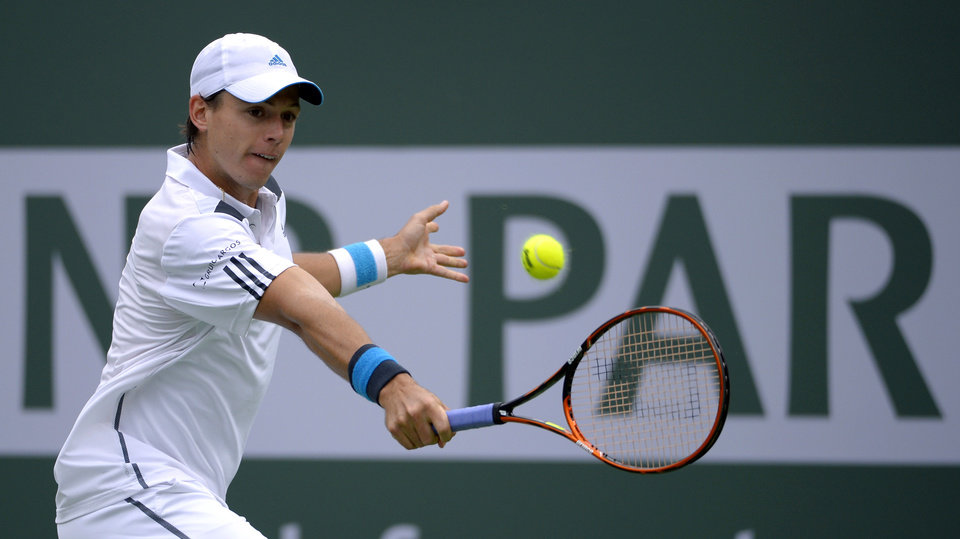Photo - Alejandro Gonzalez, of Colombia returns a shot to Novak Djokovic, of Serbia during a third round match at the BNP Paribas Open tennis tournament, Tuesday, March 11, 2014, in Indian Wells, Calif. (AP Photo/Mark J. Terrill)