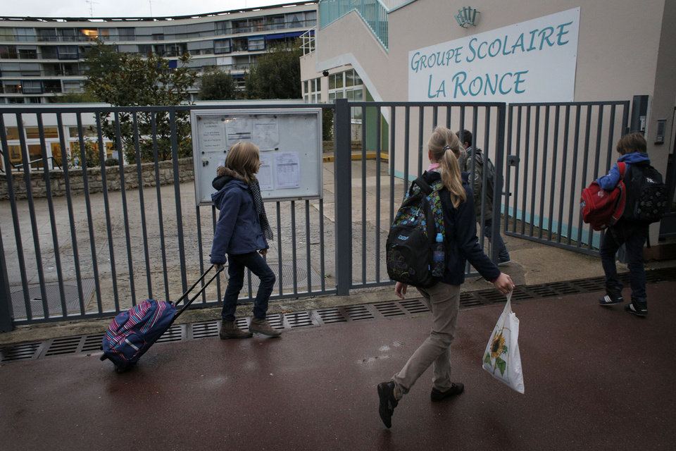 Students enter the school of La Ronce in Ville d\'Avray, west of Paris, Friday, Oct. 5, 2012. French children go to school four days a week with about two hours each day for lunch. And they have more vacation than their counterparts almost anywhere in the West. As a candidate, President Francois Hollande promised to change things by adding a fifth day of classes on Wednesday while shortening the school day and education minister, Vincent Peillon, will decide this month how to carry out the reform. (AP Photo/Christophe Ena)