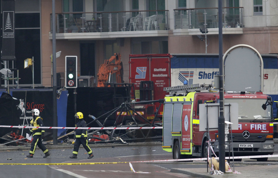 Photo - Firefighters walk pass the section of damaged crane on the ground after a helicopter crashed into the crane on top of a building in central London, Wednesday Jan. 16, 2013. Police say two people were killed when a helicopter crashed Wednesday during rush hour in central London after apparently hitting a construction crane on top of a building. (AP Photo/Sang Tan)