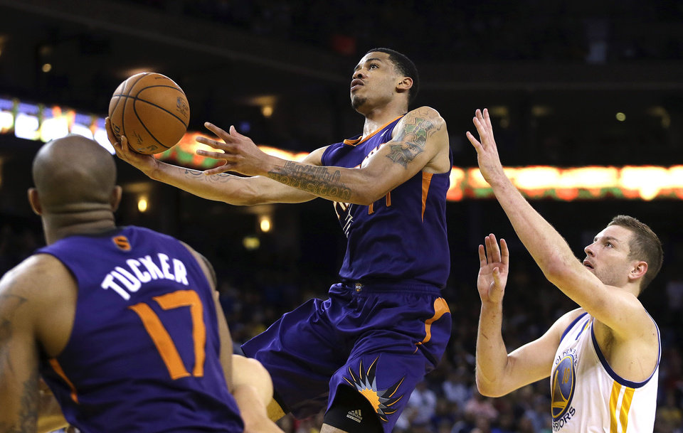 Photo - Phoenix Suns' Gerald Green, center, lays up a shot past Golden State Warriors' David Lee, right, during the second half of an NBA basketball game Sunday, March 9, 2014, in Oakland, Calif. (AP Photo/Ben Margot)