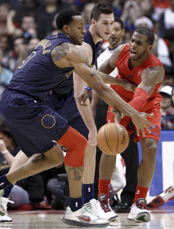 Photo - Los Angeles Clippers guard Chris Paul, right, passes the ball under pressure from Denver Nuggets' Andre Iguodala (9) and Danilo Gallinari, center, during the first half of their NBA basketball game, Tuesday, Dec. 25, 2012, in Los Angeles. (AP Photo/Jason Redmond)