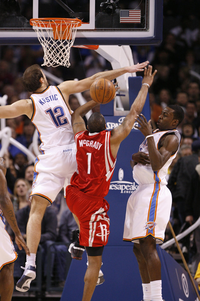 Photo - Nenad Krstic (12) and Jeff Green combine to block a shot by Tracy McGrady in the second half as the Oklahoma City Thunder plays the Houston Rockets at the Ford Center in Oklahoma City, Okla. on Friday, January 9, 2009. 
