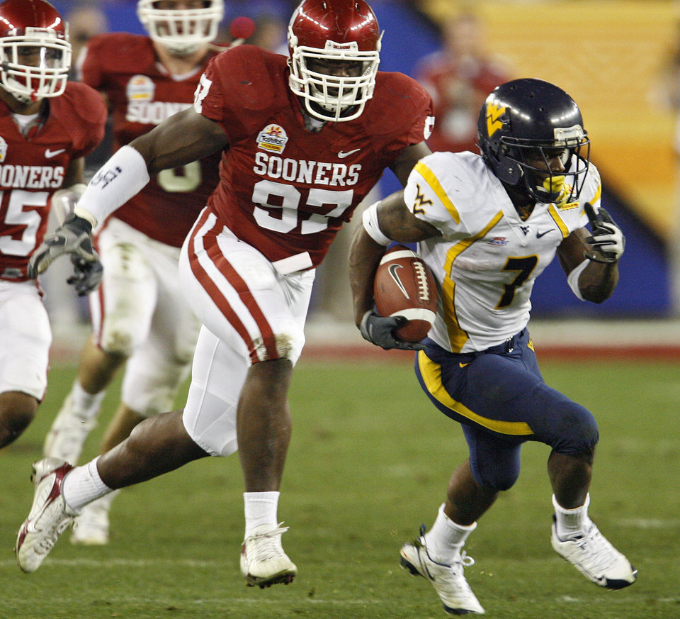 Photo - West Virgina's Noel Devine (7) out runs Oklahoma's Cory Bennett (97) during the first half of the Fiesta Bowl college football game between the University of Oklahoma Sooners (OU) and the West Virginia University Mountaineers (WVU) at The University of Phoenix Stadium on Wednesday, Jan. 2, 2008, in Glendale, Ariz. 