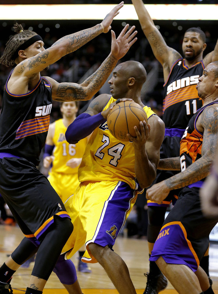 Los Angeles Lakers' Kobe Bryant (24) is pressured by Phoenix Suns' Michael Beasley, left, Shannon Brown (6), and Markieff Morris (11) during the first half on an NBA basketball game, Wednesday, Jan. 30, 2013, in Phoenix. (AP Photo/Matt York)