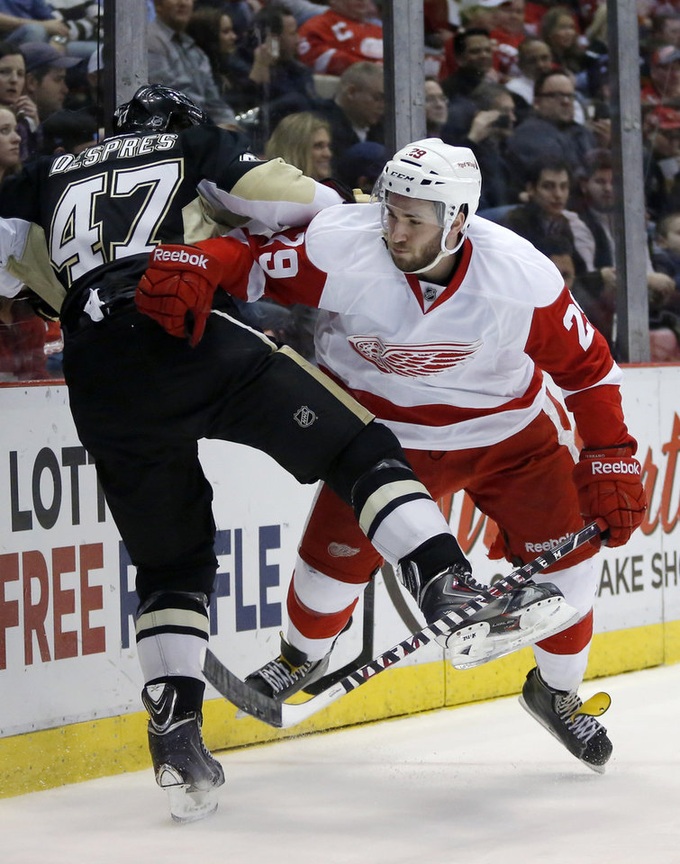 Photo - Pittsburgh Penguins' Simon Despres (47) is pushed against the boards by Detroit Red Wings' Landon Ferraro (29) during the second period of an NHL hockey game Thursday, March 20, 2014, in Detroit. (AP Photo/Duane Burleson)