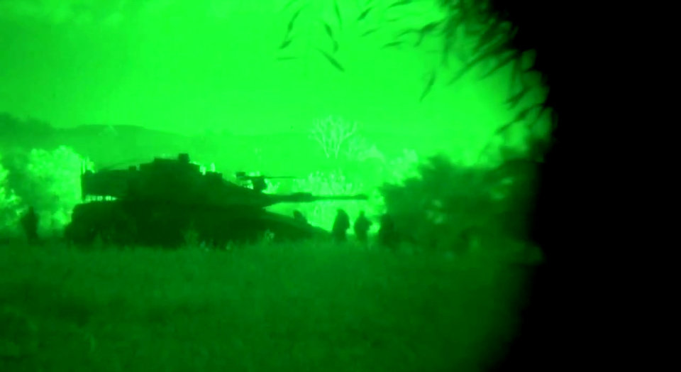 Photo - This image made from video shot through a night vision scope released by the Israeli military on Friday, July 18, 2014 shows a tank in the Gaza Strip during a ground offensive. Israeli troops pushed deeper into Gaza on Friday to destroy rocket launching sites and tunnels, firing volleys of tank shells and clashing with Palestinian fighters in a high-stakes ground offensive meant to weaken the enclave's Hamas rulers. (AP Photo/Israeli Defense Forces)