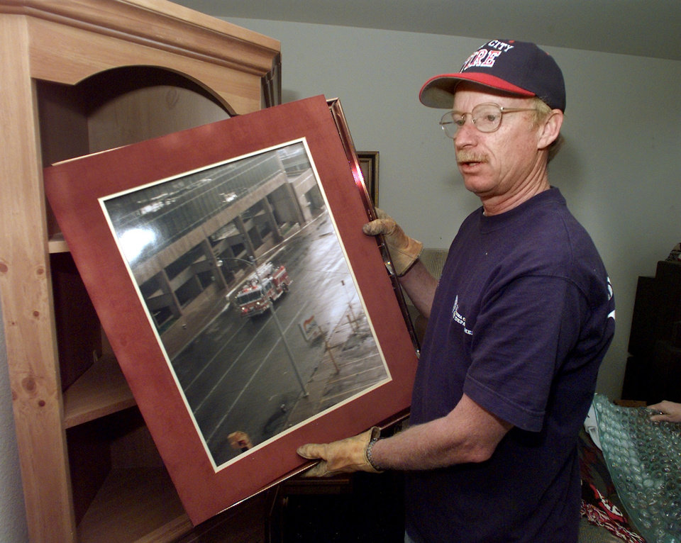 Tornado victims, damage: Assistant Fire Chief Jon Hansen in his house that was hit by the tornado. The photo is of the Murrah building about a week before the bombing. Goes with Robert Medley's Sunday story.