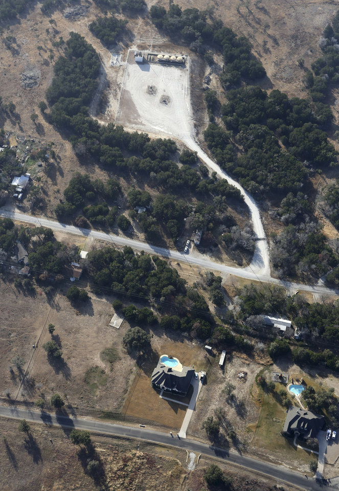 "Photo - This Dec. 6, 2012 aerial photo shows a natural gas well, top, in rural Parker County near Granbury, Texas. The U.S. Environmental Protection Agency had evidence the gas company's drilling operation contaminated nearby drinking water with explosive methane, and possibly cancer-causing chemicals, but withdrew its enforcement action, leaving households with no useable water supply, according to a report obtained by The Associated Press. The EPA's decision to roll back its initial claim that hydraulic fracturing, or ""fracking,"" operations had contaminated the water is the latest case in which the federal agency initially linked drilling to water contamination and then softened its position, drawing criticism from Republicans and industry officials who insisted they proved the agency was inefficient and too quick to draw conclusions. (AP Photo/LM Otero)"
