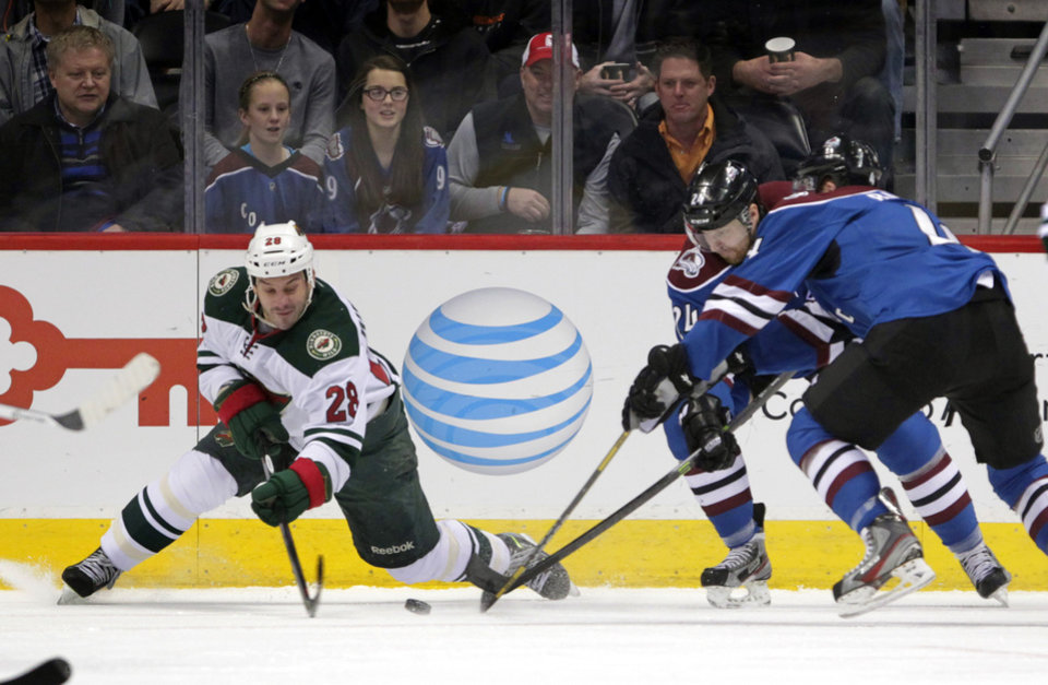 Photo - Minnesota Wild center Zenon Konopka (28) reaches for the puck against Colorado Avalanche right wing Marc-Andre Cliche (24) and Avalanche defenseman Tyson Barrie, right, during the first period of an NHL hockey game in Denver on Saturday, Dec. 14, 2013. (AP Photo/Joe Mahoney)