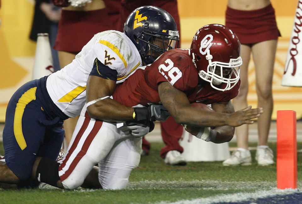 Photo - Oklahoma's Chris Brown (29) is brought down by West Virginia's Ryan Mundy (21) during the second half of the Fiesta Bowl college football game between the University of Oklahoma Sooners (OU) and the West Virginia University Mountaineers (WVU) at The University of Phoenix Stadium on Wednesday, Jan. 2, 2008, in Glendale, Ariz. 