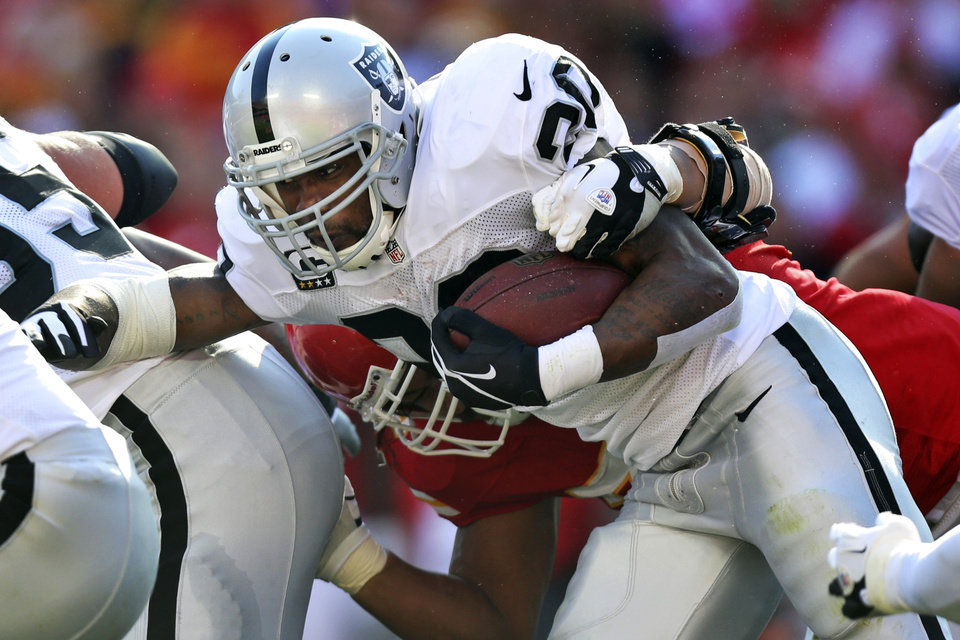 Photo -   Oakland Raiders running back Darren McFadden (20) is tackled by Kansas City Chiefs defensive end Glenn Dorsey during the first half of an NFL football game at Arrowhead Stadium in Kansas City, Mo., Sunday, Oct. 28, 2012. (AP Photo/Ed Zurga)