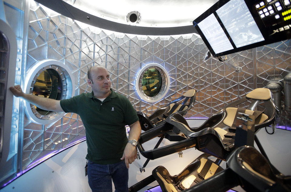Photo -  Garrett Reisman, program leader for crew vehicles of the SpaceX, stands inside the SpaceX Dragon V2 Thursday at the headquarters in Hawthorne, Calif. AP Photo   Jae C. Hong -  AP