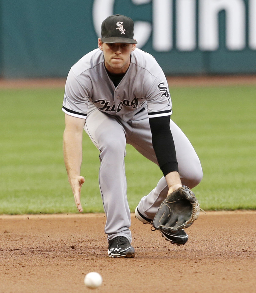 Photo - Chicago White Sox's Conor Gillaspie fields a ball hit by Cleveland Indians' Nick Swisher in the first inning of a baseball game, Monday, July 29, 2013, in Cleveland. Swisher was out at first base. (AP Photo/Tony Dejak)