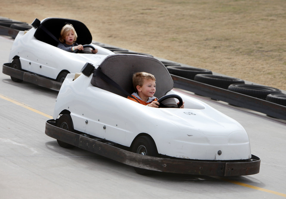 Calob Williams (front) and Griffin Shelton race cars during a community fair at Andy's Alligator Park in Norman, OK, Saturday, Nov. 12, 2011. By Paul Hellstern, The Oklahoman