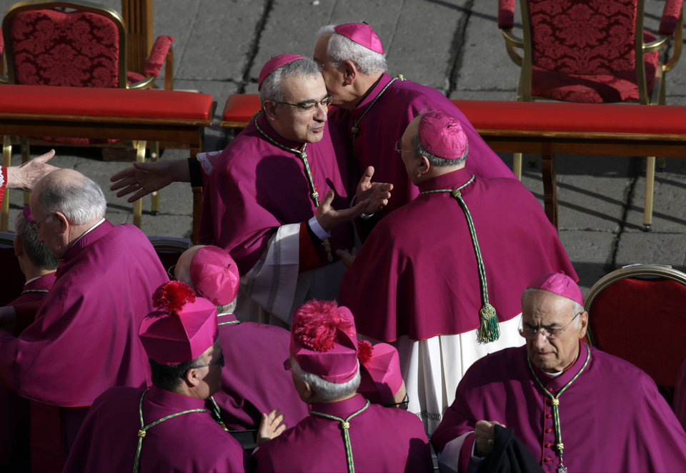 Bishops arrive to take their seats in St. Peter's Square for the inaugural Mass of Pope Francis, at the Vatican, Tuesday, March 19, 2013. (AP Photo/Andrew Medichini)