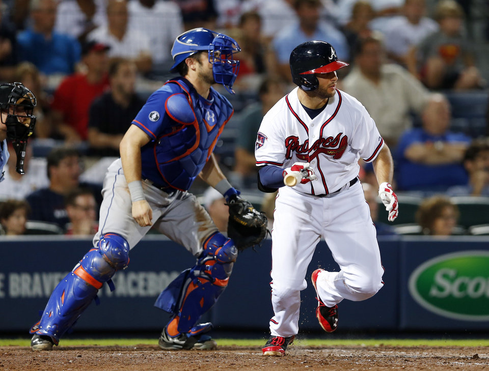 Photo - Atlanta Braves' Tommy La Stella (7) ties the game with a two-run single in the eight inning as New York Mets catcher Travis d'Arnaud (15) looks on in the eighth inning of a baseball game in Atlanta, Monday, June 30, 2014. Atlanta won 5-3. (AP Photo/John Bazemore)