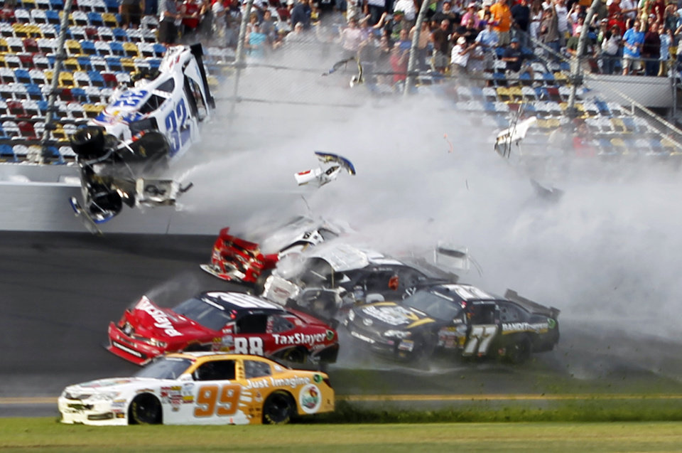 Kyle Larson (32) goes into the catch fence during a crash involving, among others, Justin Allgaier (31), Brian Scott (2), Parker Klingerman (77) and Dale Earnhardt Jr. (88) at the conclusion of the NASCAR Nationwide Series auto race Saturday, Feb. 23, 2013, at Daytona International Speedway in Daytona Beach, Fla. Getting past is Alex Bowman (99). (AP Photo/Terry Renna)
